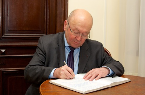 Ambassador Remek writing a note in the distinguished visitors' book